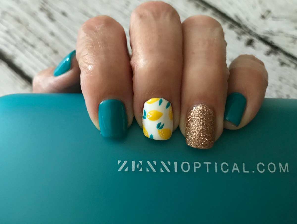 Lemon nail art holding Zenni Optical glasses