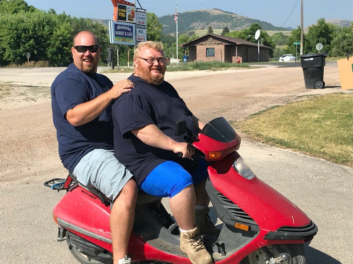 Two large men on a scooter