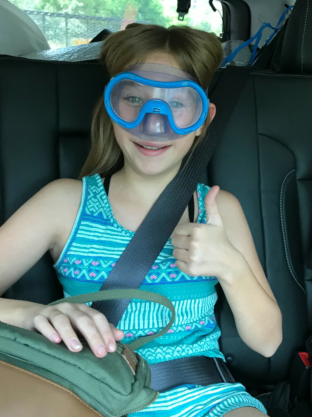 Girl wearing swim goggles in the car