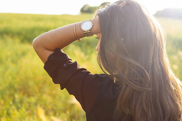 Woman wearing watch in a field.