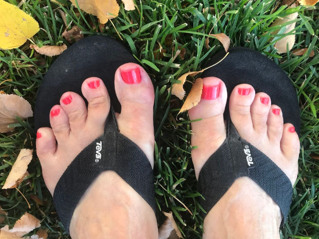 Feet with painted toenails in leaves.