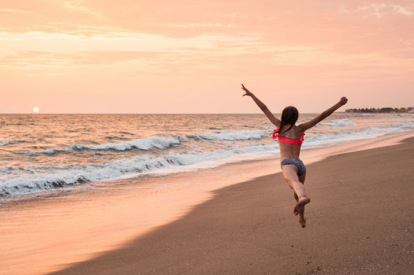 Girl leaping on the beach at sunset.
